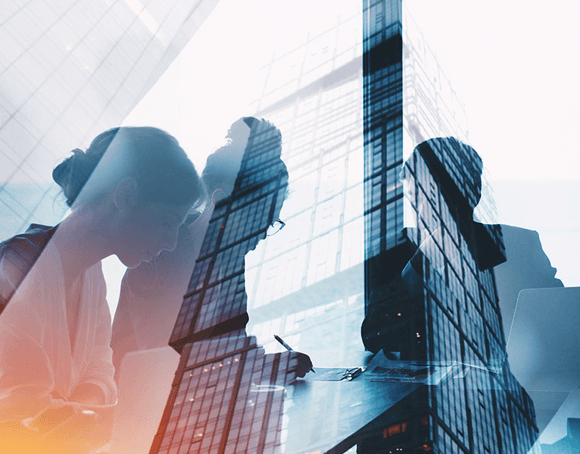 Silhouette von Personen die an einem Schreibtisch arbeiten. Das Bild ist überlagert von der Ansicht eines Bürogebäudes.
